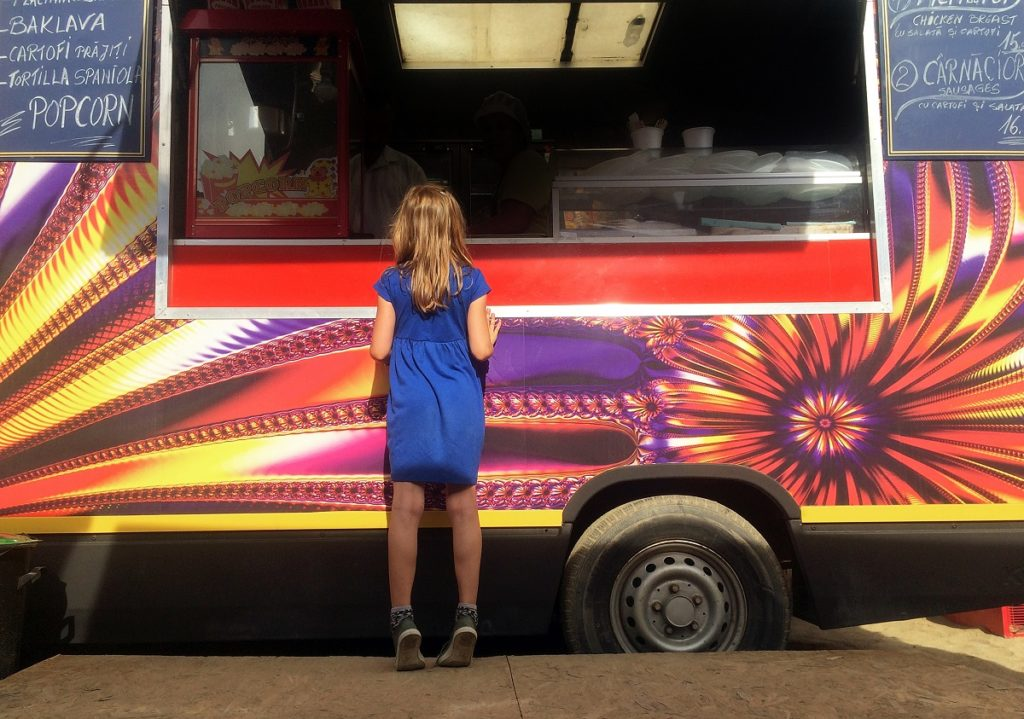 Girl standing in front of a food truck