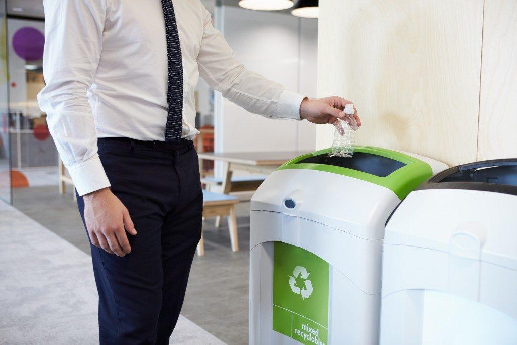 business man throwing plastic bottle in recycling bin