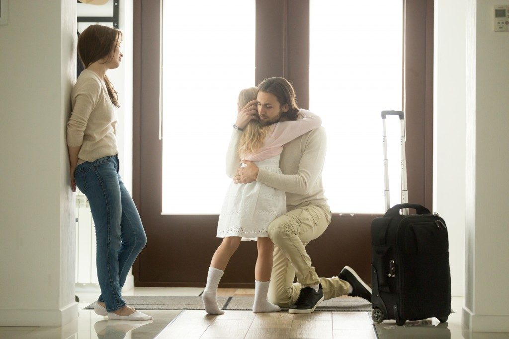 husbang with a suitcase hugging his daughter before leaving