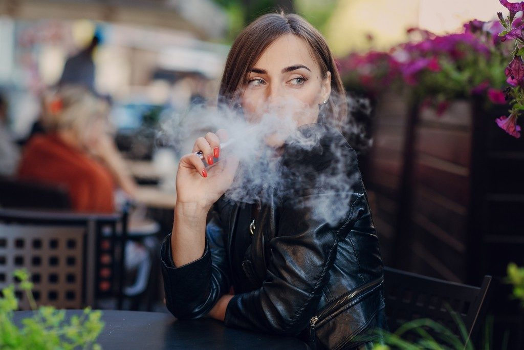 woman using vaping product outdoors