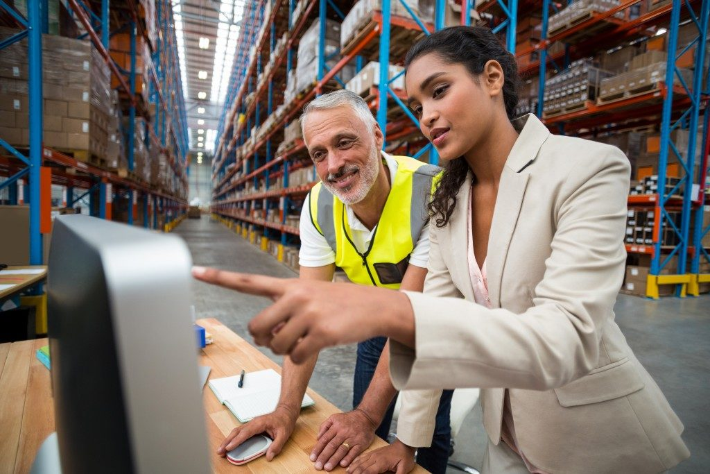 man and woman in a warehouse looking at a computer
