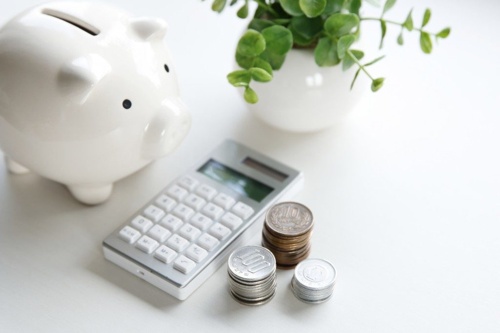 Piggy bank, calculator and coins