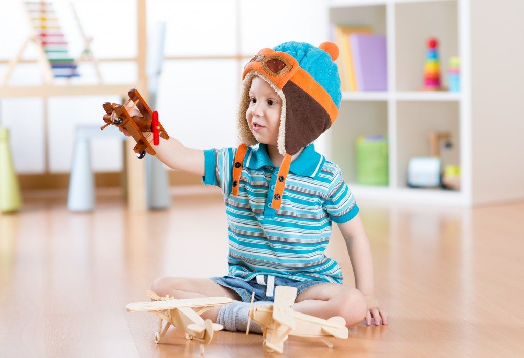 kid playing with wooden airplanes